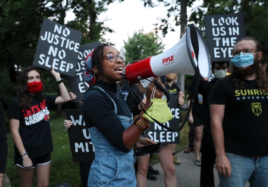 """A Sunrise activist speaks into a megaphone while fellow protesters stand behind holding signs saying """"No Justice No Sleep"""" and """"Look Us In The Eyes""""."""